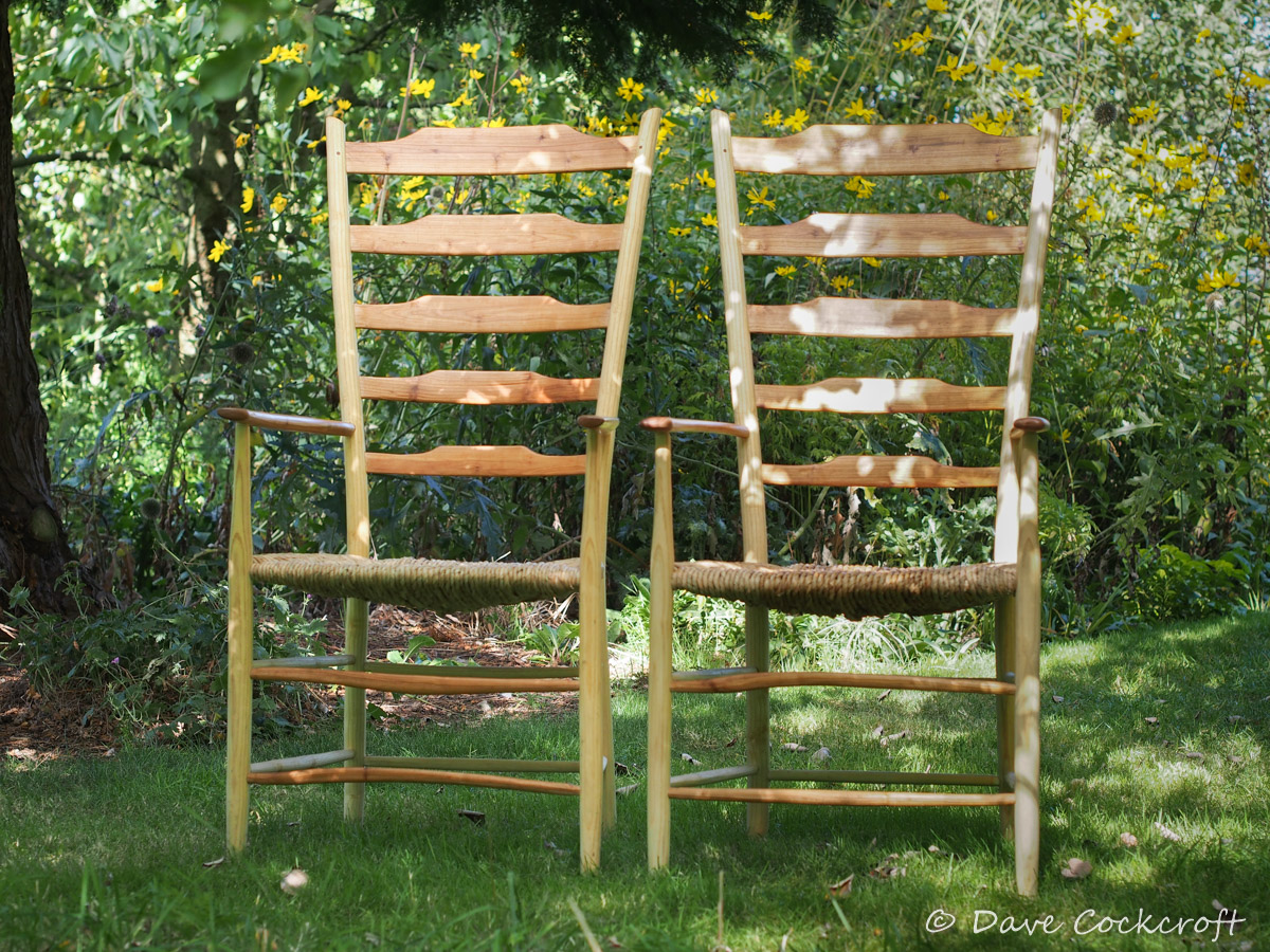 Pair of ash and cherry ladderback armchairs with rush seats